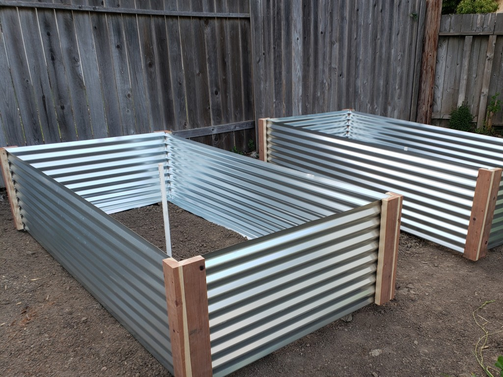 Positioning each raised metal garden bed over its spot and eyeballing the layout