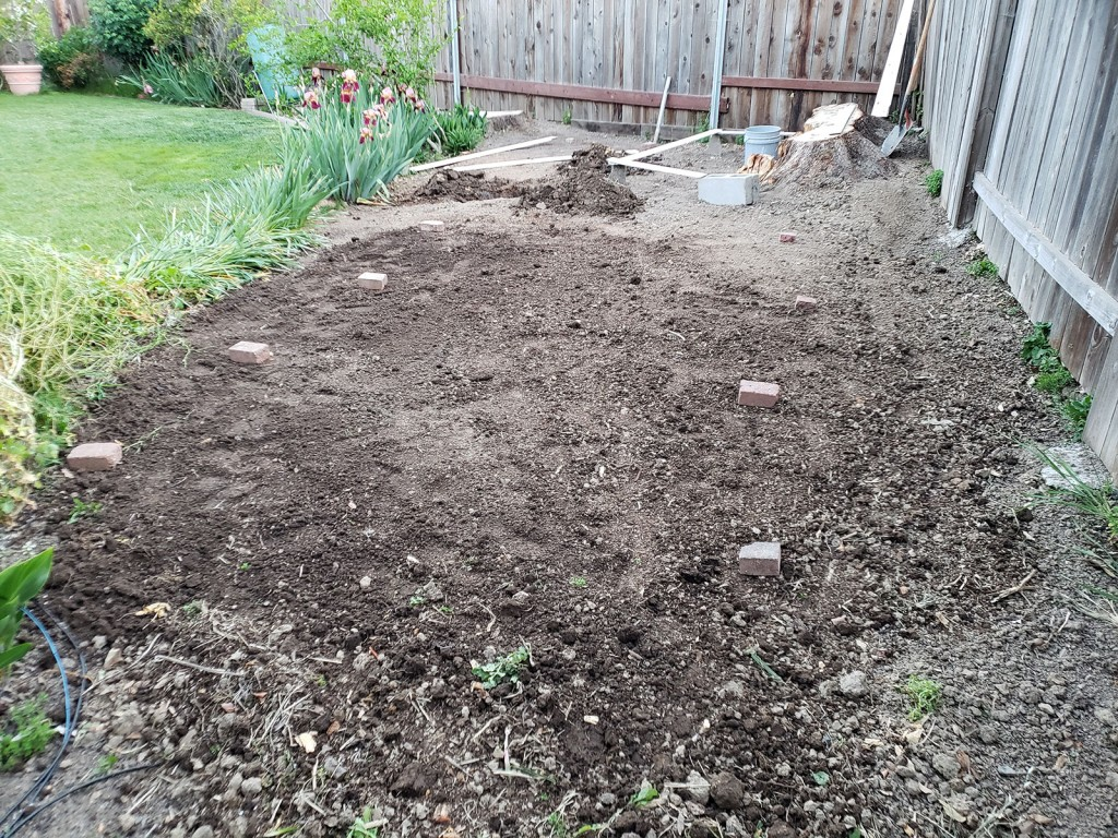 Planning raised bed layout with old bricks and scrap wood