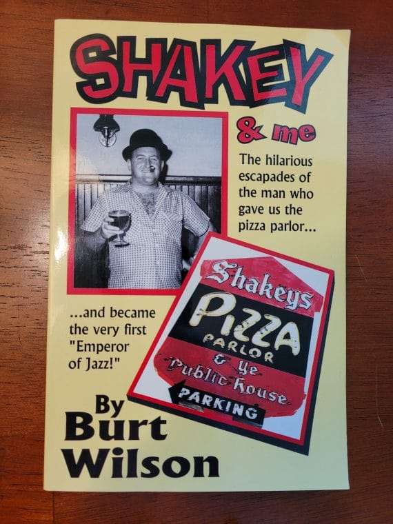 """Shakey & me [paperback] [signed] 2 sherwood (shakey) johnson founded the successful chain of shakey's pizza parlors in 1954 in sacramento, california. He became the pizza king of the us and then gave it all up to """"just have fun""""--which meant promoting dixieland jazz and becoming the first """"emperor of jazz"""" in 1973 at the world's largest traditional jazz jubilee in his hometown of sacramento. Author burt wilson, life-long friend, confidant and advertising agent and pr man for shakey's recalls all the hilarious incidents and funny stories which made shakey a legend in his own time."""