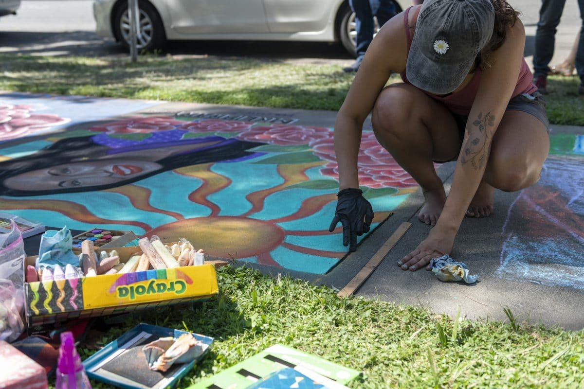 Mariah drawing a black outline around her chalk square